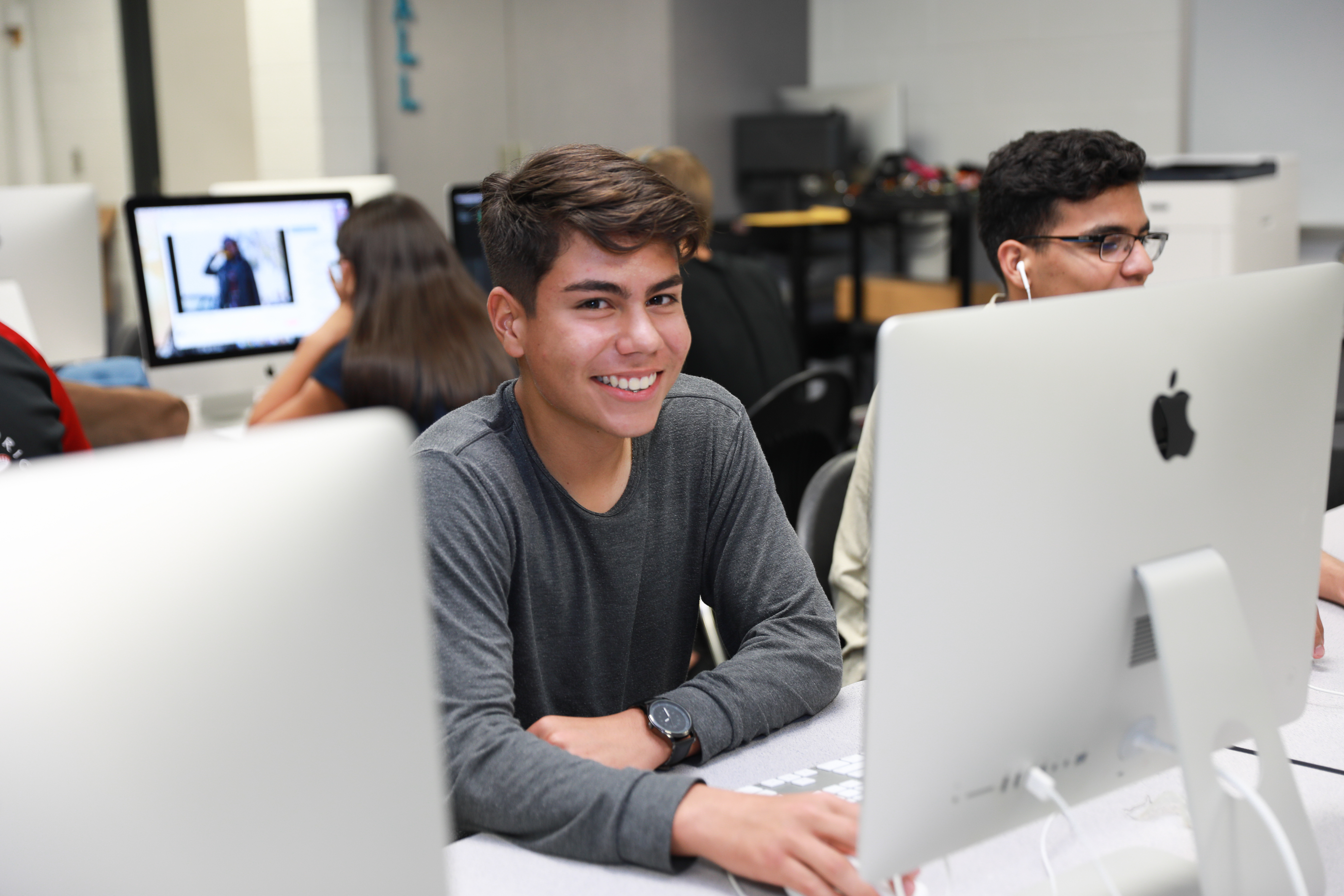 Teenager smiling at the camera with other students working in a computer lab